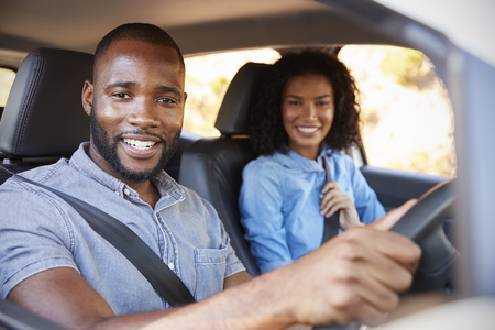 Young black couple in a car on a road trip smiling to camera