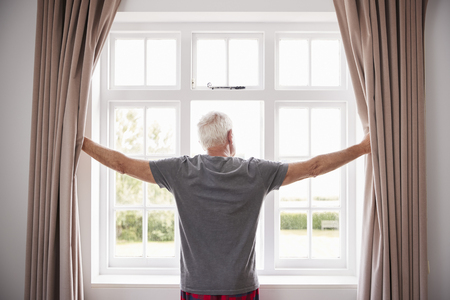 Senior Man Opening Bedroom Curtains And Looking Out Of Window