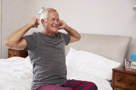 Senior Man Waking Up And Stretching In Bedroom
