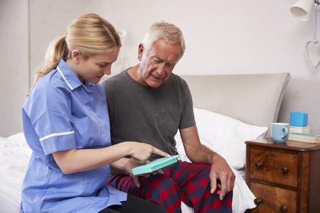 infirmière aidant homme âgé pour organiser les médicaments sur la maison de paris Banque d'images