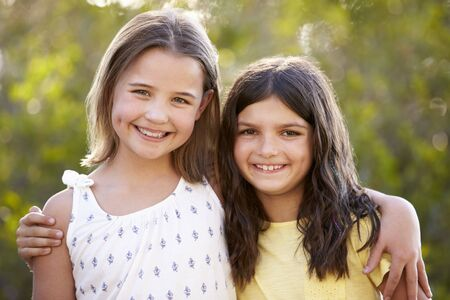 Portrait of two happy young girls embracing outdoors Banco de Imagens - 96250987