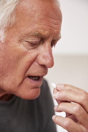 Senior Man Sitting On Bed At Home Taking Medication Stock Photo
