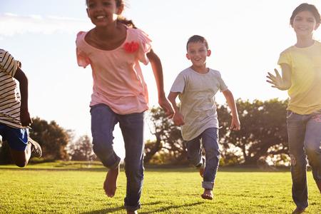 Three happy children running barefoot in a field in Summer