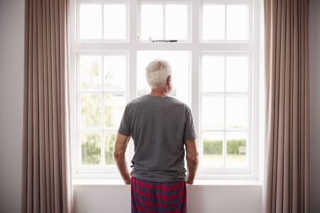 Rear View Of Senior Man In Pajamas Looking Out Of Bedroom Window