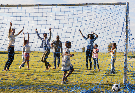 Two families playing football in park celebrating a goal