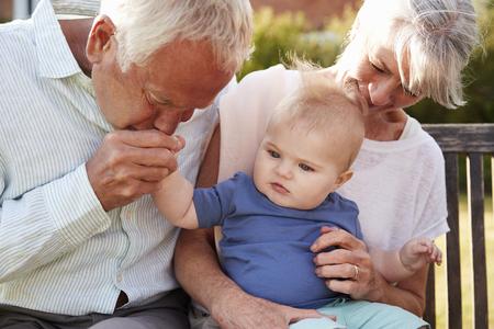 Dziadkowie siedzą na siedzeniu w ogrodzie z małym wnukiem