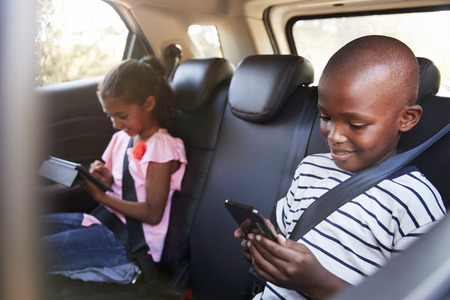 Boy and girl in a car using tablet and smartphone on a trip Banco de Imagens