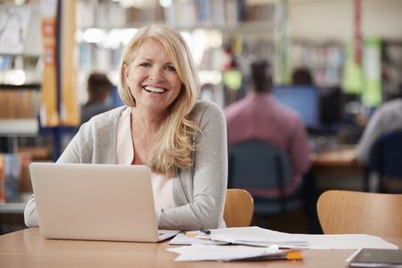 Retrato de estudiante maduro usando la computadora portátil en la biblioteca