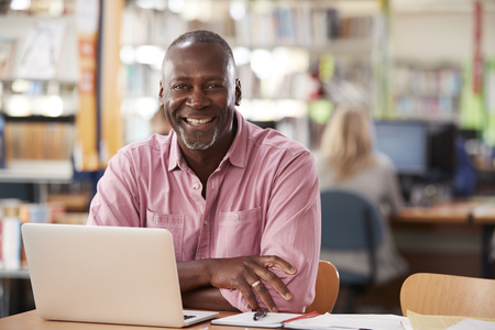 Portrait Of Mature Male Student Using Laptop In Library Stok Fotoğraf - 96254759