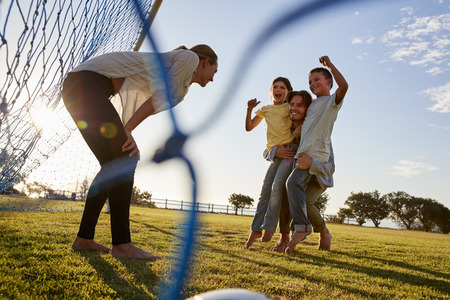 Dad lifts his son and daughter during a family football game Stock Photo