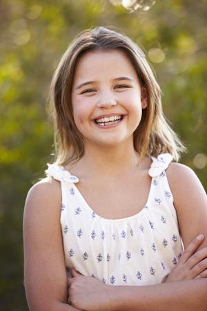 屋外でカメラを見ている笑う若い女の子の肖像画 写真素材