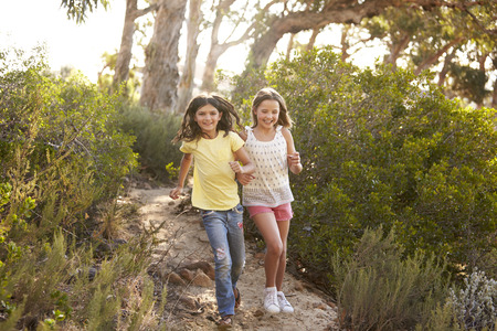 Two smiling young girls running in a forest in the sun