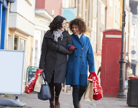 Two Mature Female Friends Enjoying Shopping In City Together