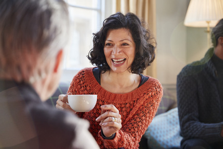 Middle Aged Woman Meeting Friends Around Table In Coffee Shop Stockfoto