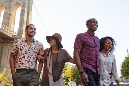 Grupo de amigos caminando por el puente de Brooklyn en la ciudad de Nueva York