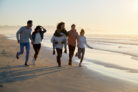 Group Of Friends Having Fun Running Along Winter Beach Together Stok Fotoğraf