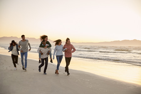 Group Of Friends Having Fun Running Along Winter Beach Together Stok Fotoğraf - 97223489