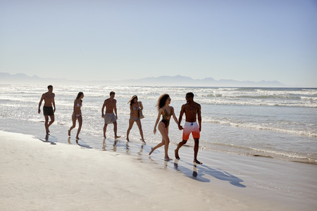 Group Of Friends Walking Through Waves On Beach Vacation