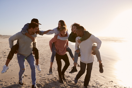 Group Of Friends Having Piggyback Race On Winter Beach Together Stock Photo