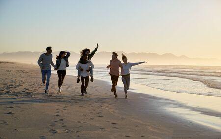 Group Of Friends Having Fun Running Along Winter Beach Together Stok Fotoğraf - 97223783