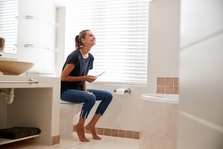 Woman In Bathroom Celebrates Positive Home Pregnancy Test Result Stock fotó