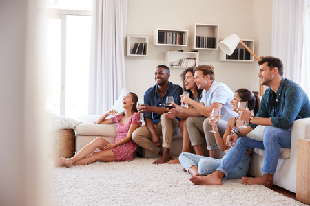 Group Of Friends Relaxing At Home Watching TV Together Stock Photo