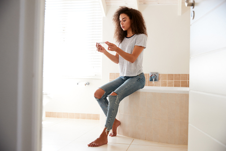 Concerned Woman In Bathroom With Home Pregnancy Test