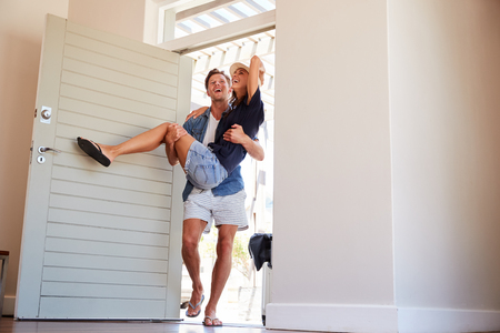 Man Carries Woman Over Threshold Of Honeymoon Rental Reklamní fotografie - 97225231