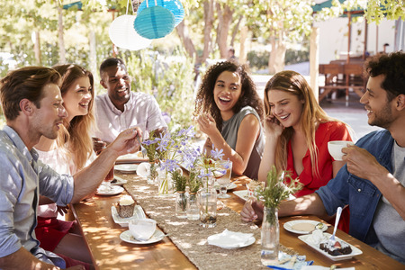 Six young friends dining at a table outdoors