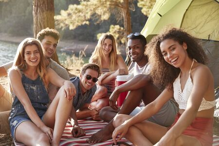 Friends relaxing on a blanket by a lake, close up Stock Photo