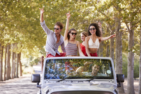 Friends having fun standing in the back of an open top car