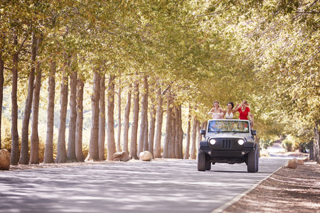 Friends driving on an empty road in an open top jeep