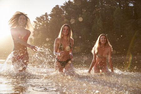 Three female friends on vacation having fun in a lake