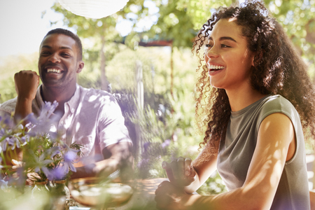 Young adult friends sitting at a table in a garden laughing