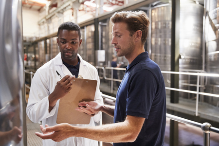 Two men talk and inspect vats in a modern winemaking factory