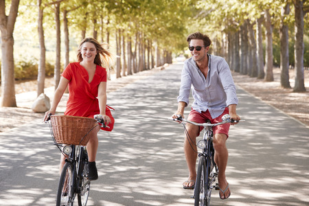 Young white adult couple riding bikes on a tree lined road Stock Photo