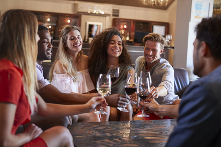 Six young adults making a toast with wine at a bar Stock Photo - 97564224