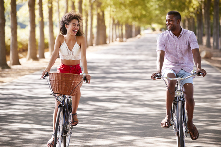 Laughing young couple riding bicycles on a sunny road