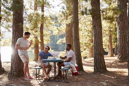 Three male friends hanging out talking by a lake Stock Photo