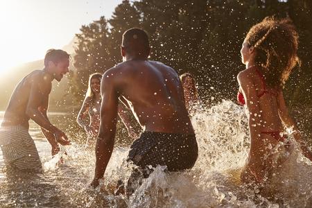 Young adult friends on vacation splashing in a lake Reklamní fotografie