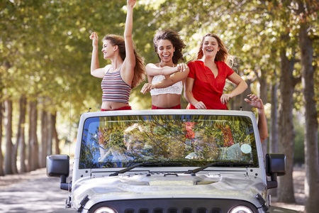 Girlfriends standing in an open top car with arms in the air