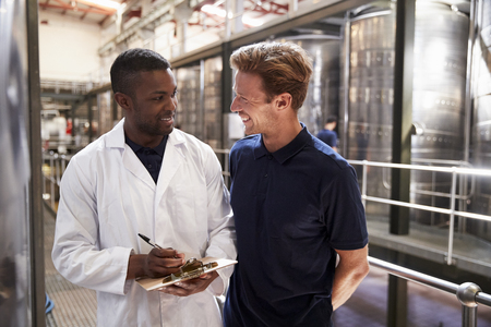 Two men smiling during an inspection in a winemaking factory