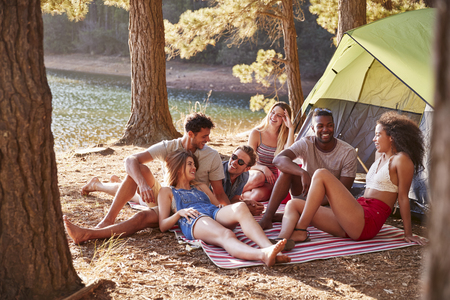 Friends on a camping trip relaxing on a blanket by a lake