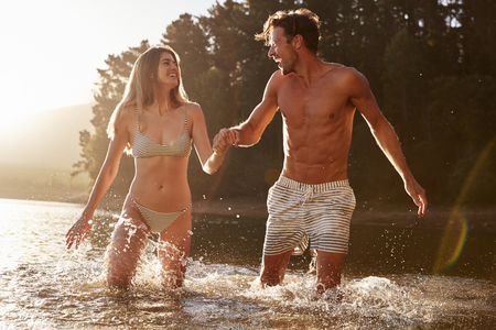 Young white couple smiling at each other standing in a lake Stock Photo