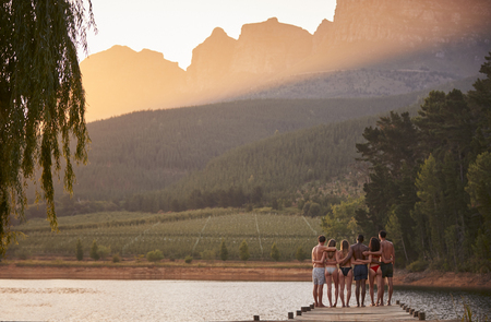 Group of friends hanging out by the lake, back view Stock Photo