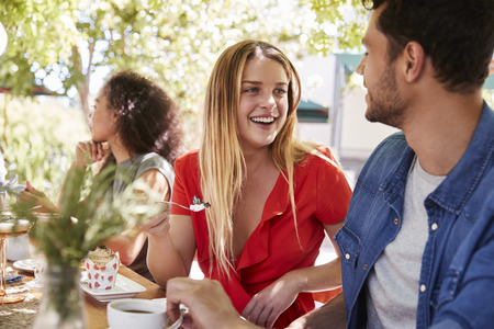 Three young adult friends dining at a table outdoors