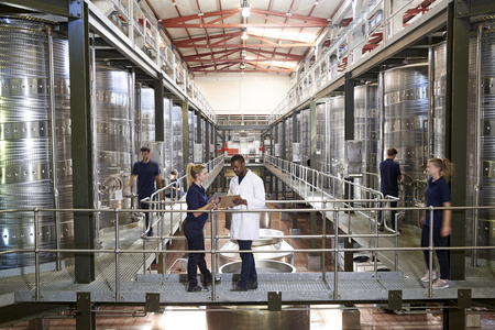 Two staff talking on gangway in a modern winemaking factory Stock Photo