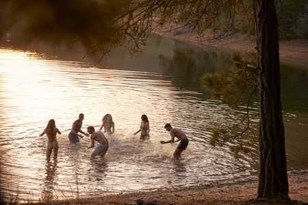 Young adult friends splashing and having fun in a lake Stock Photo