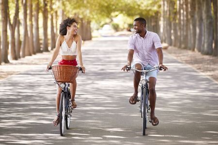Young mixed race couple riding bicycles looking at each other