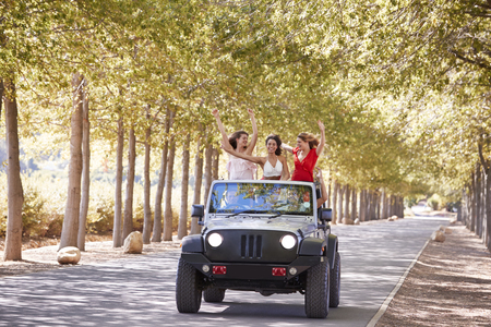 Girlfriends standing up in the back of an open top vehicle Stock Photo